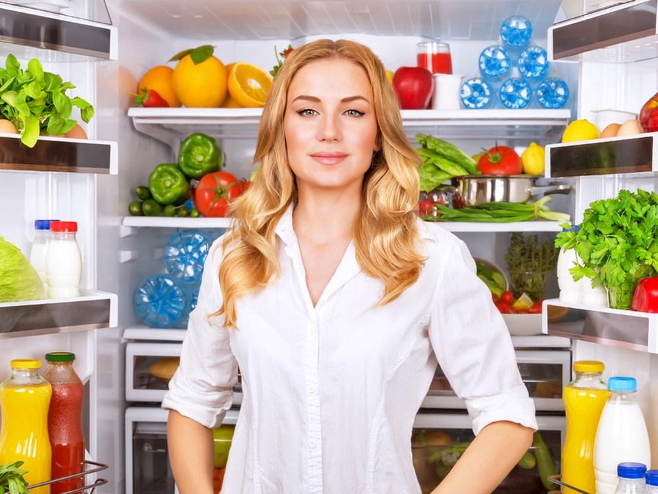 Portrait of cute serious female standing near open fridge full of healthy food, vegetables and fruits, healthy lifestyle concept